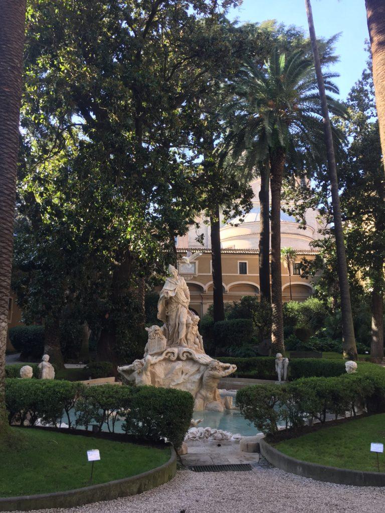 """Malá zahrada uvnitř paláce - """"giardino interno"""" s malým jezírkem se sousoším, s palmami a krátce střiženým trávníkem."""