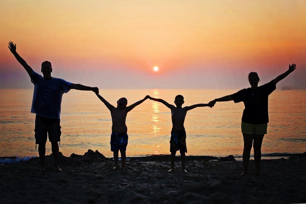 Štastná rodinka - rodiče a dvě děti při západu slunce na pobřeží moře.