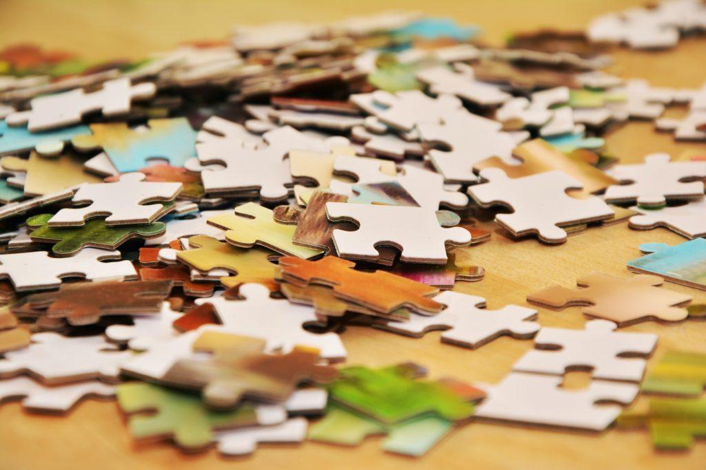 Různobarevné dílky puzzlí, rozházené po stole.