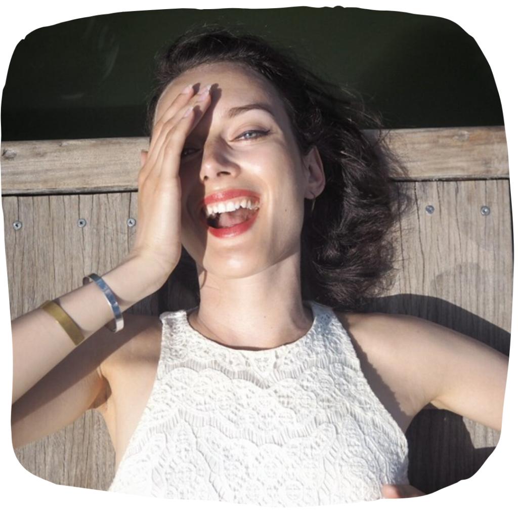 Profilová fotka Lucie van Koten. Lucie leží asi na molu, směje se do objektivu.