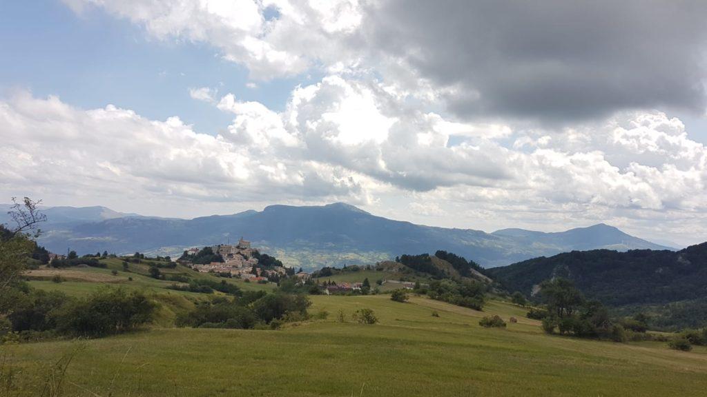 Abruzzo, místní příroda - hory, zelená louka a městečko.