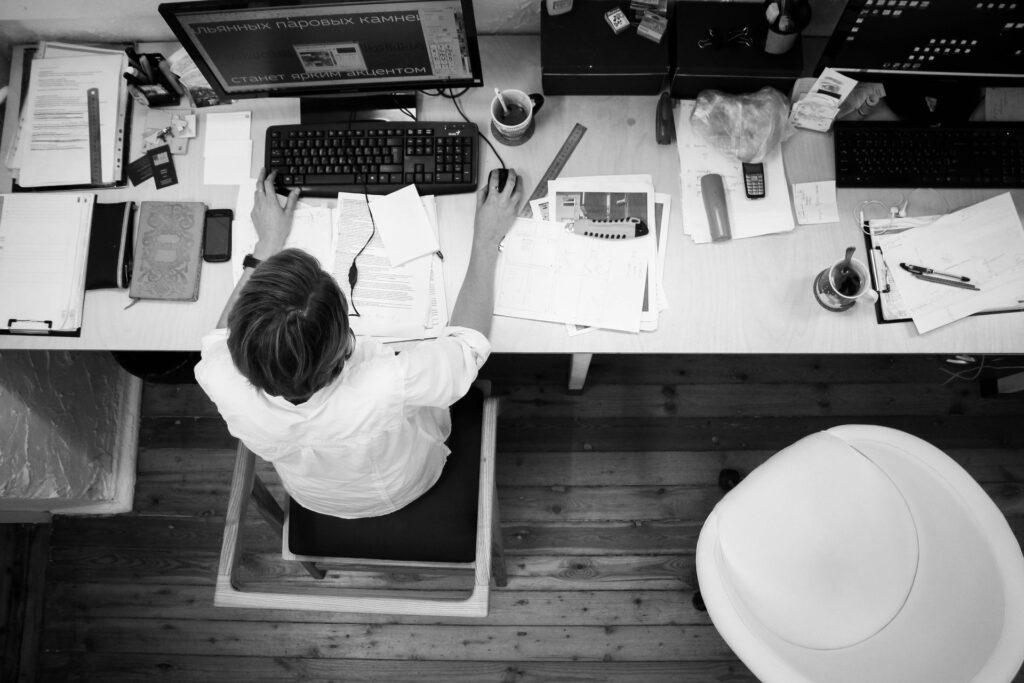 Pohled shora na pracovní stůl, černobilý snímek.