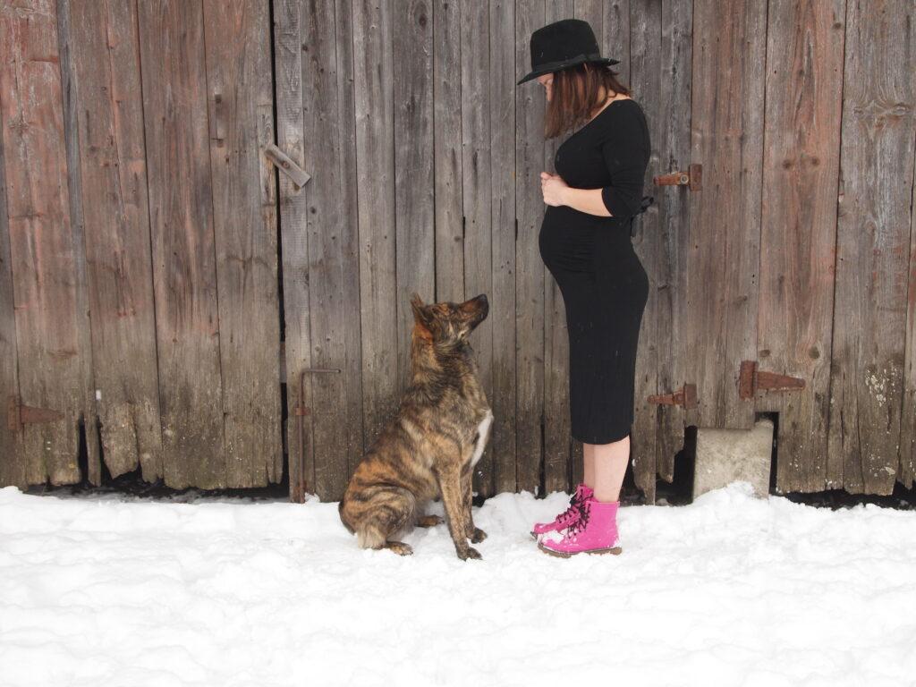 Těhotná Julia v černých šatech a s kloboukem. Před ní sedí pes.