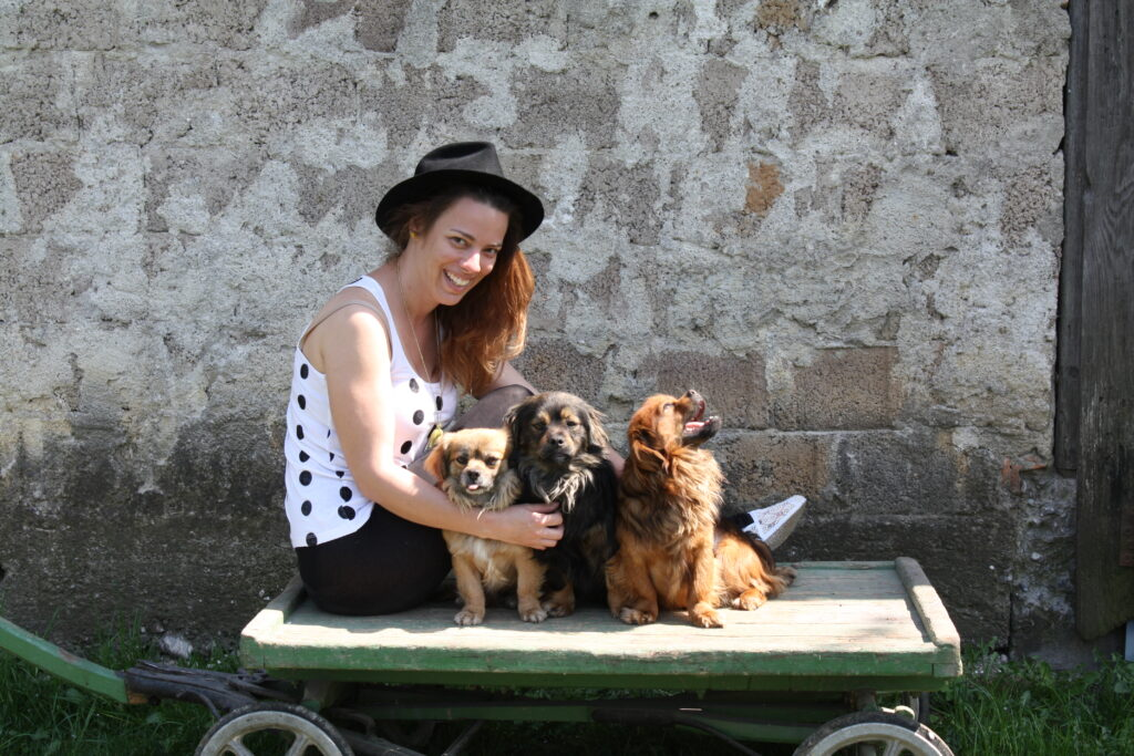 Júlie u zdi, sedí na vozíku se čtyřmi koly spolu se 3 psy.