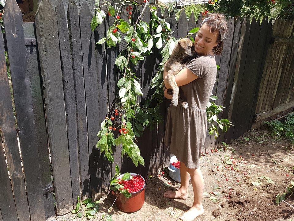 Júlia drží v náručí  štěňátko a na zemi leží kyblíky s třešněmi.