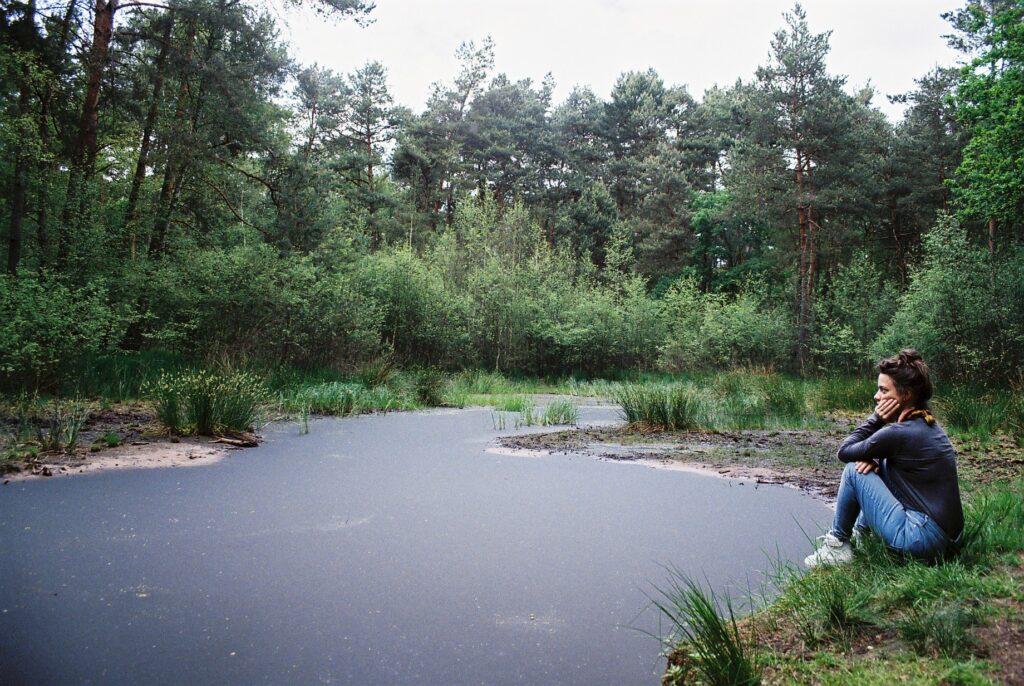 Júlia u rybníka, zamyšleně sedí na zemi.