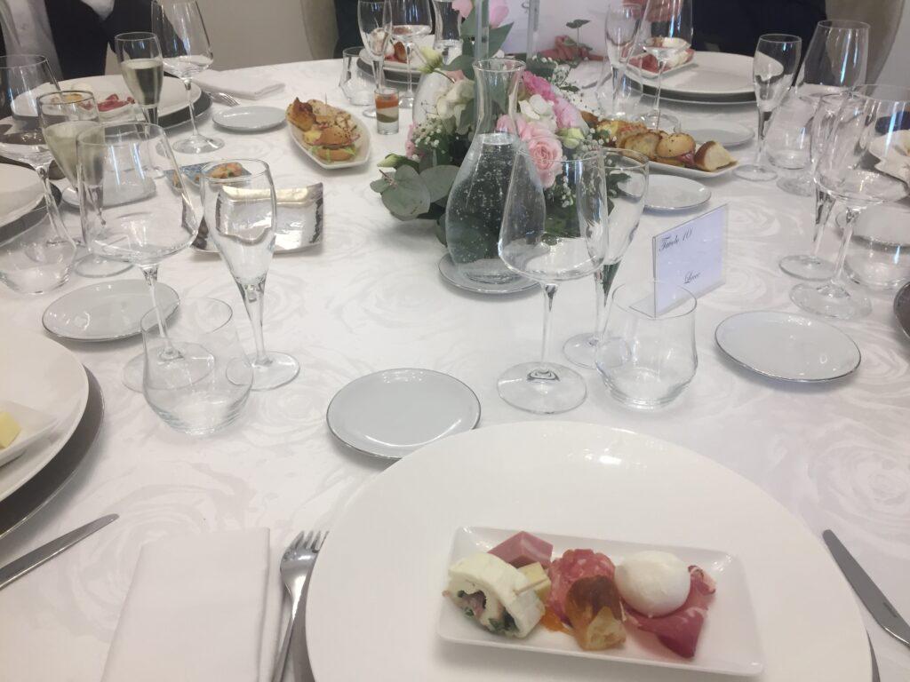 Svátečně nazdobený svatební stůl s květinami, laděnými do růžova.