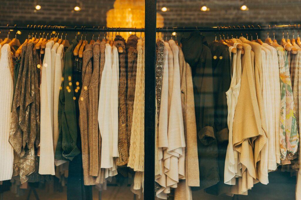Dámské oblečení, vystavené v obchodě. Hnědé cihly v pozadí.