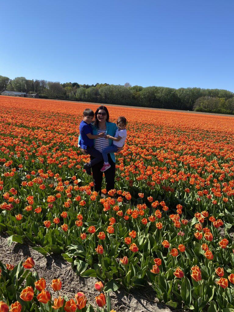 Helena se svými 2 dětmi v poli, plném rozkvetlých tulipánů.