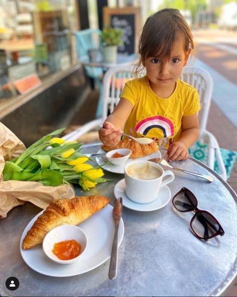 Dcera Heleny na snídani venku, na stole croissanty a tulipány.