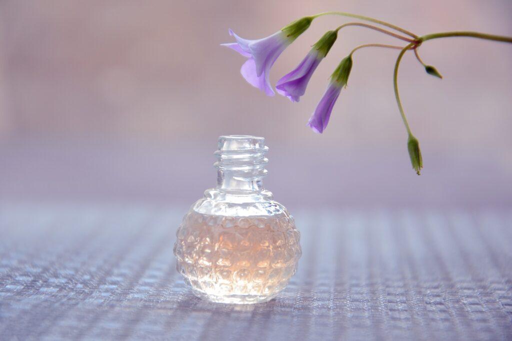 Malá lahvička s parfémem, položená na ubruse. Nad ní je květina, zvonek.