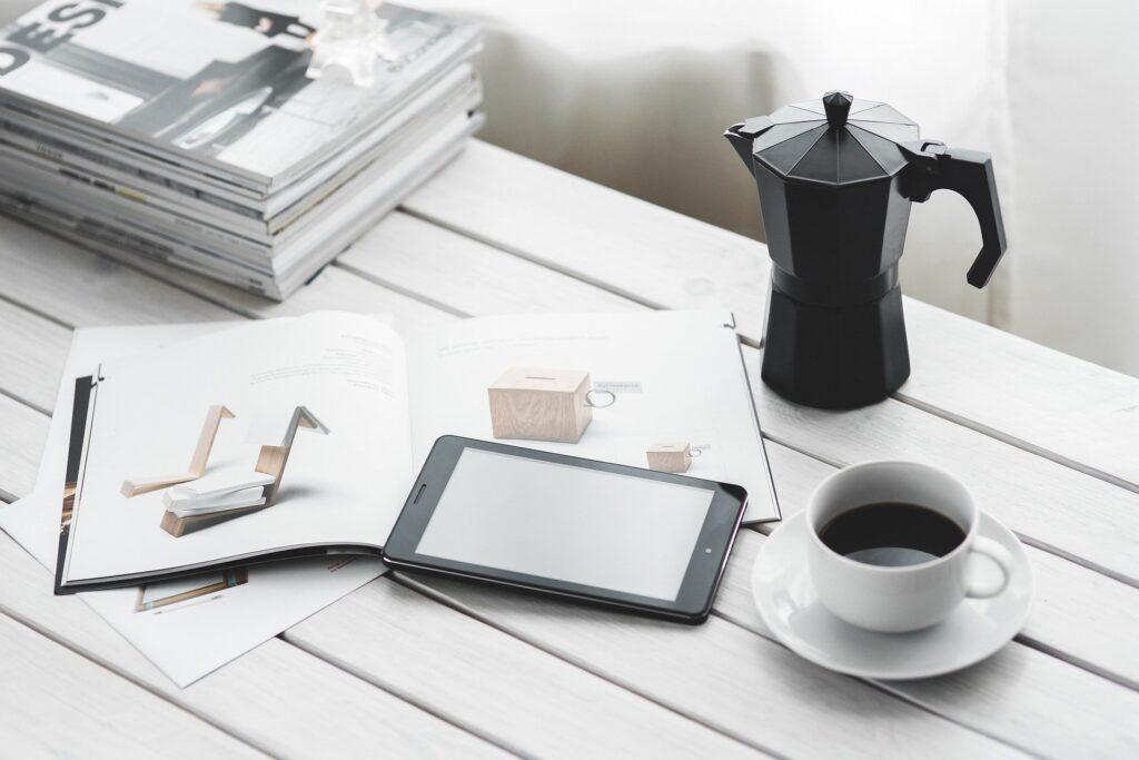 Italská kávová konvička caffettiera položená na dřevěném stole. Vedle stojí hrnek kávy.