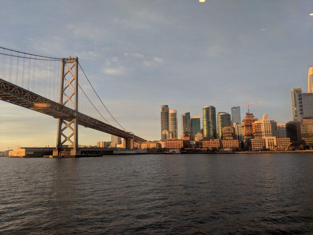 Výhled přes řeku na americké velkoměsto a majestátný most.