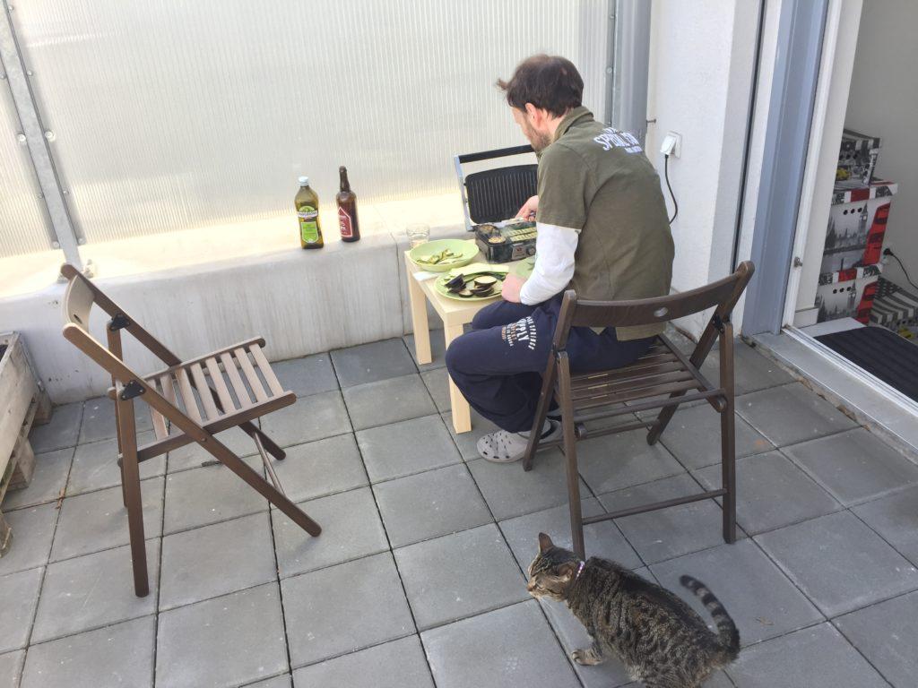 Můj Ital připravuje grilovanou cuketu za asistence naší kočky a lahve piva.