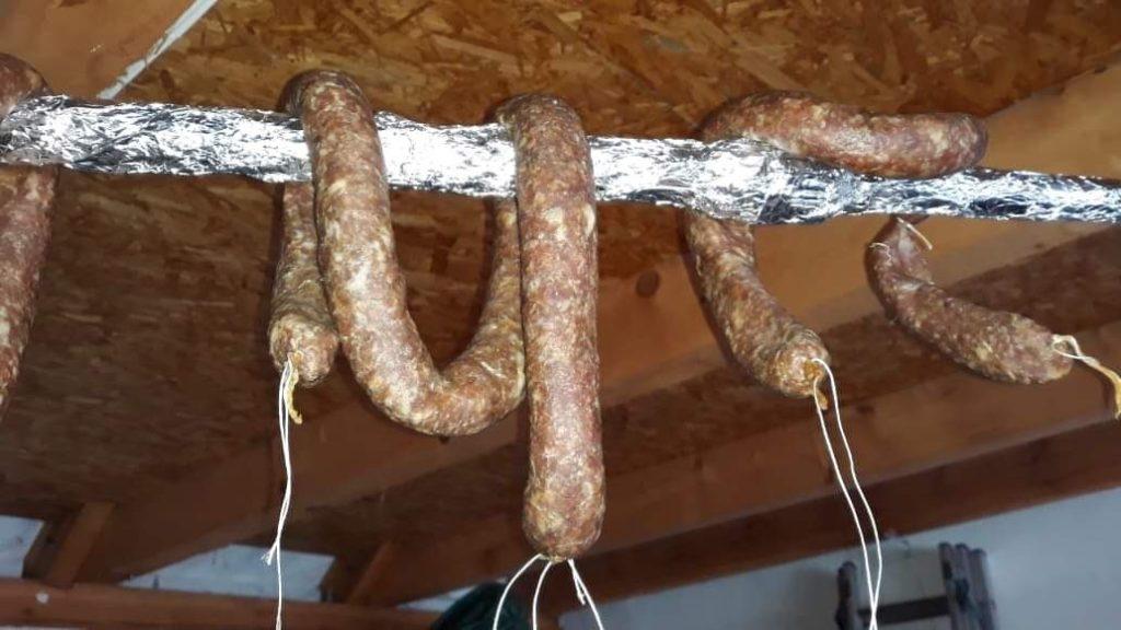 doma vyrobená salsiccia, zavěšená na tyči v garáži