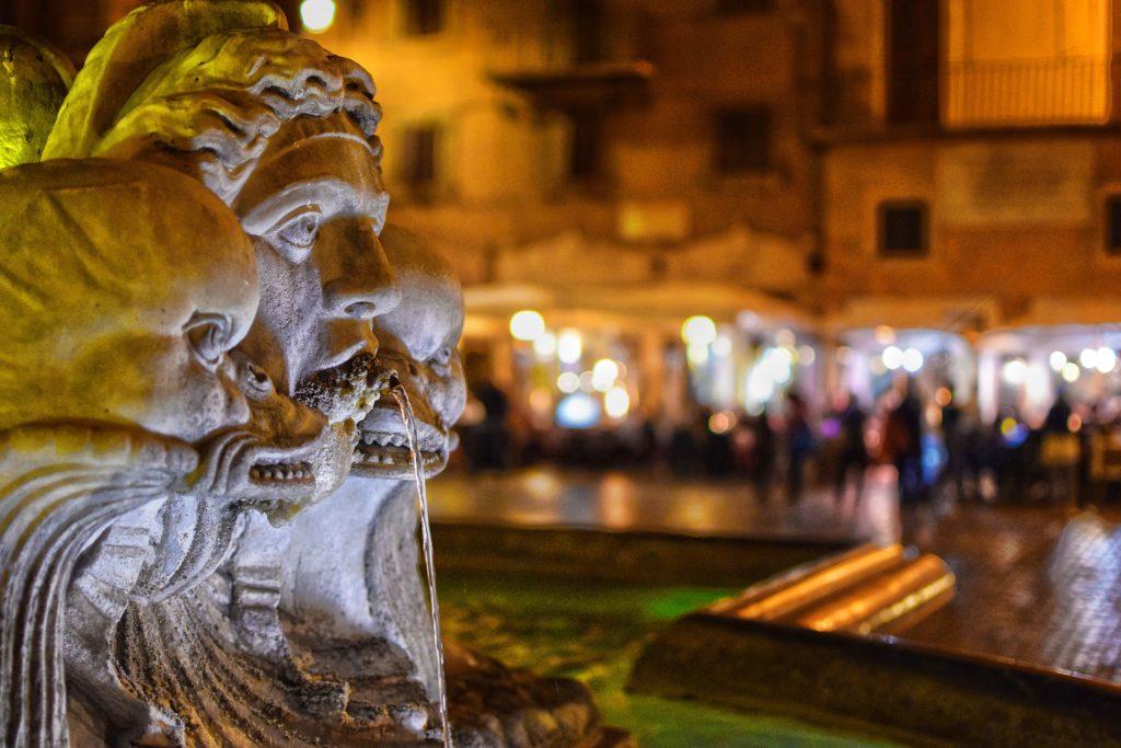 Jedna z římských fontán ve večerním světle, v pozadí náměstí Piazza Navona.