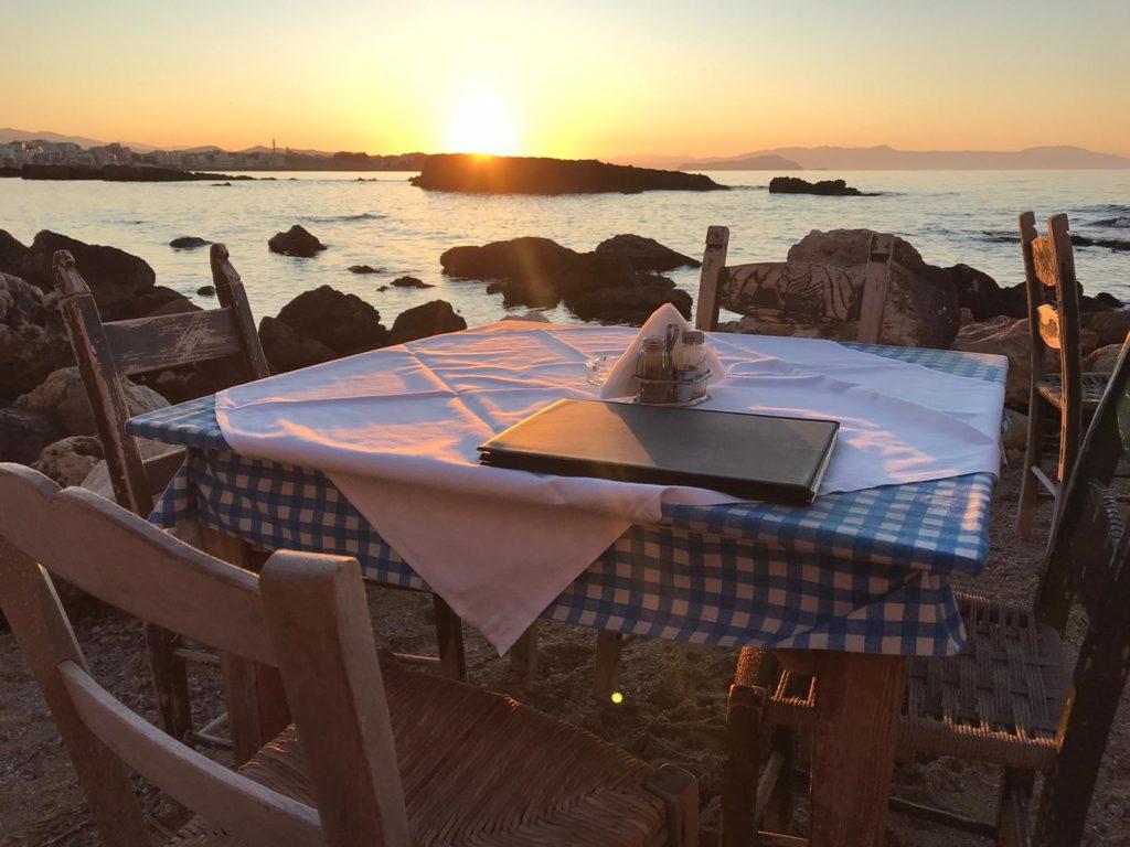 prostřený stůl při západu slunce na pobřeží, v pozadí moře