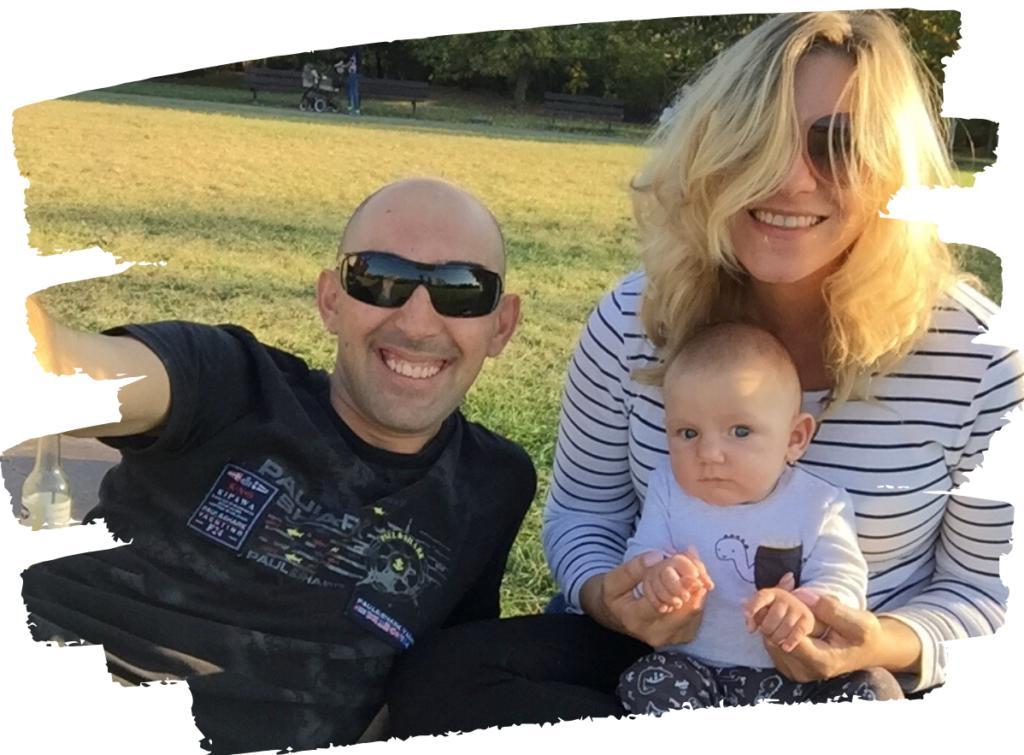 Dita s manželem a s prckem, na trávě v parku.