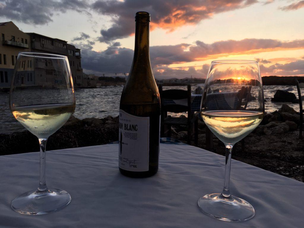 dvě skleničky vína a láhev, na pozadí moře a západ slunce