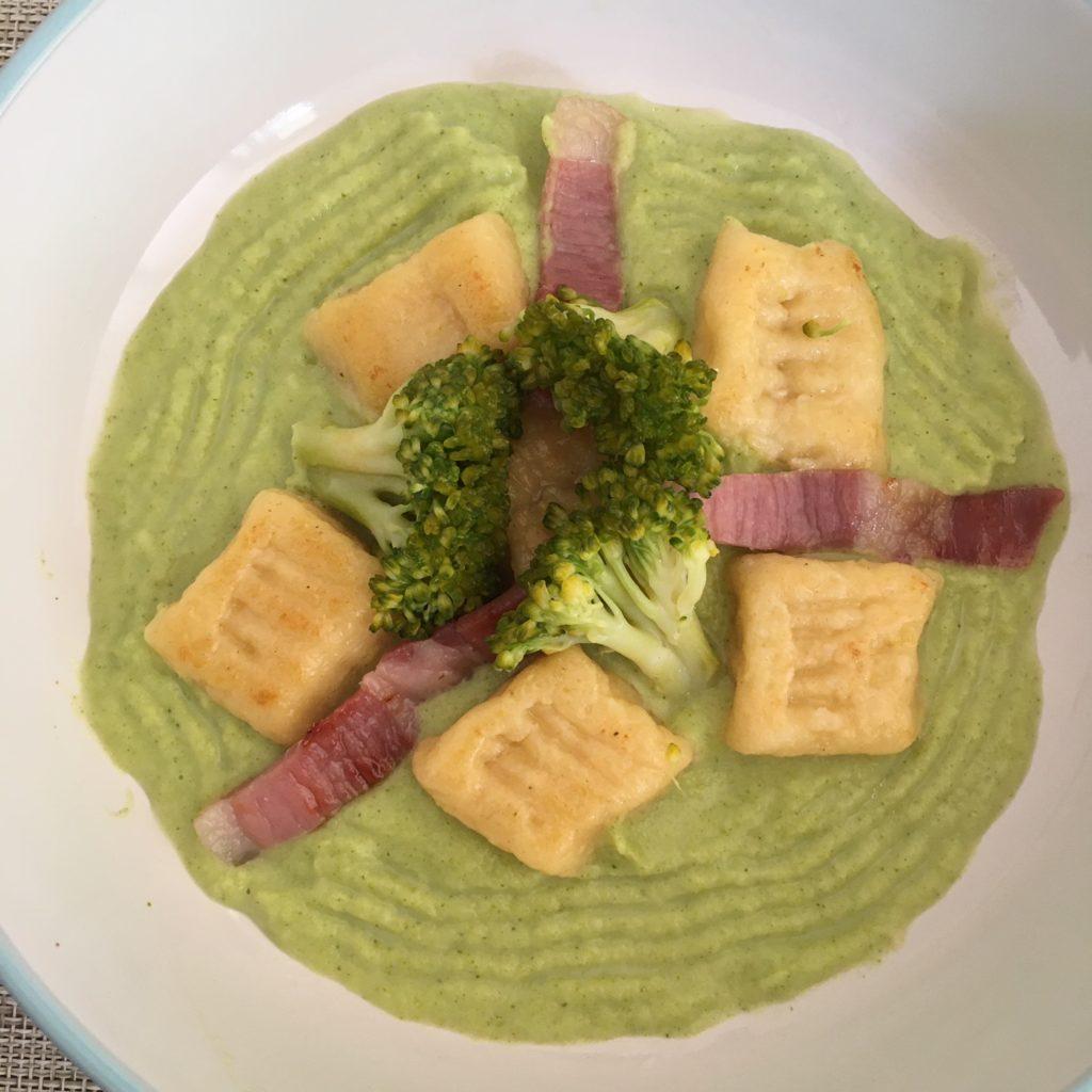 """Hotový pokrm společně s brokolicovou """"omáčkou"""" a kousky celé brokolice a opraženou šunkou."""