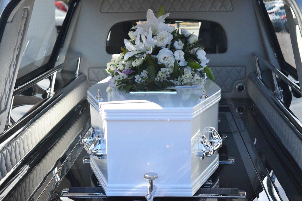 bílá rakev s květinovou ozdobou uvnitř pohřebního auta