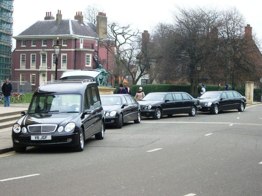 kolona pohřebních aut, jedno s otevřeným víkem kufru