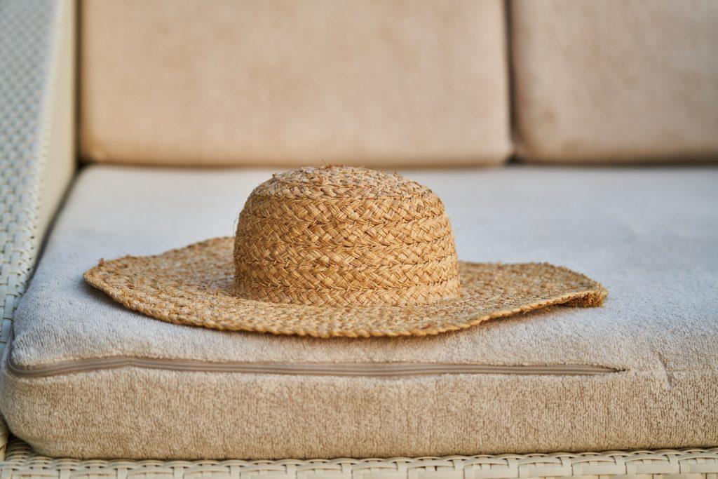 slaměný klobouk, ležící na gauči