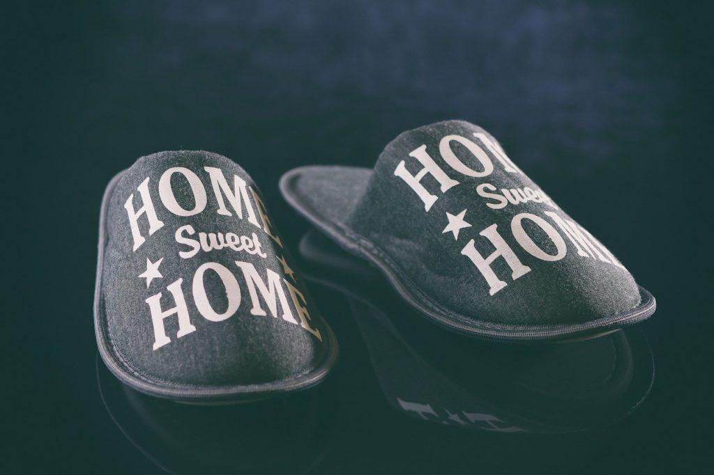 Domácí přezůvky šedé barvy, položené na lesklé podlaze.