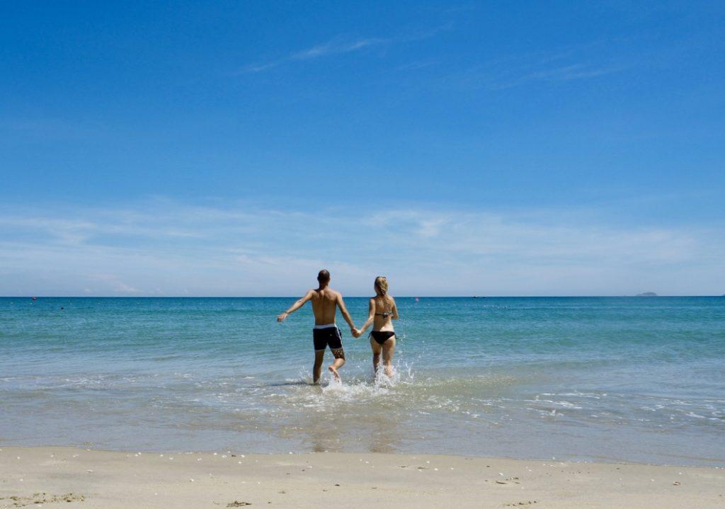 Barča a Marco vbíhají do moře z písčité pláže, slunečný den.