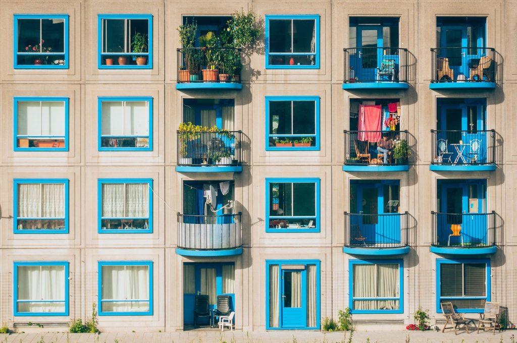 Balkony s kulatým zábradlím a modře orámovanými okny.