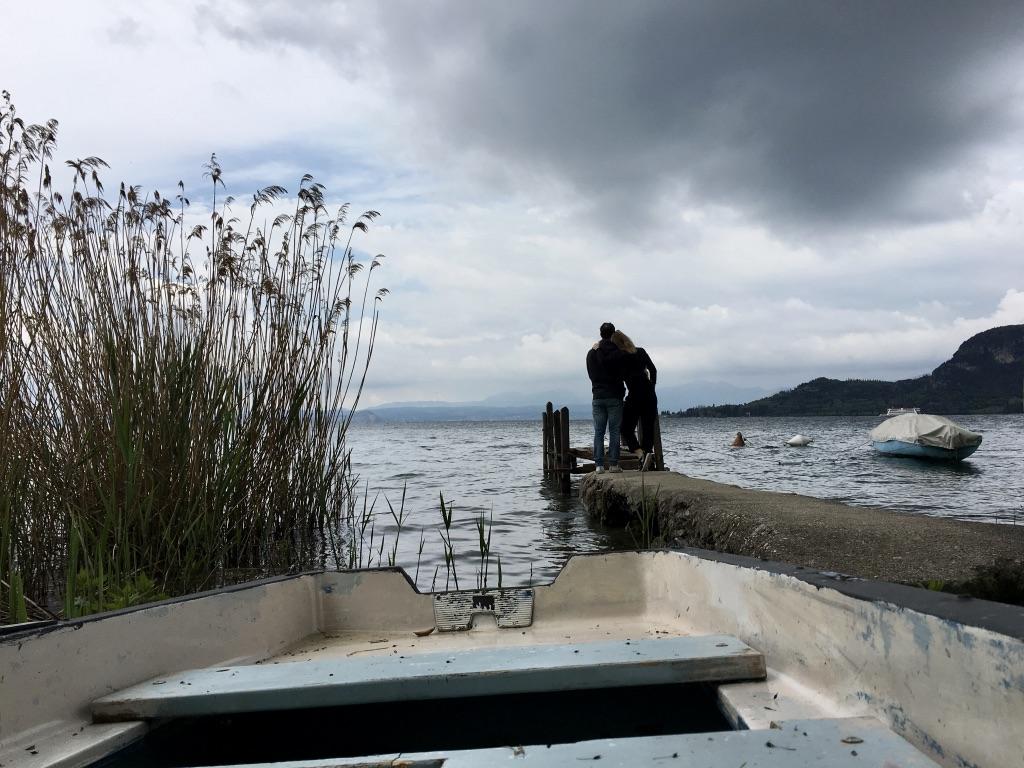 Barča a Marco na molu pod zataženým nebem, u jezera.