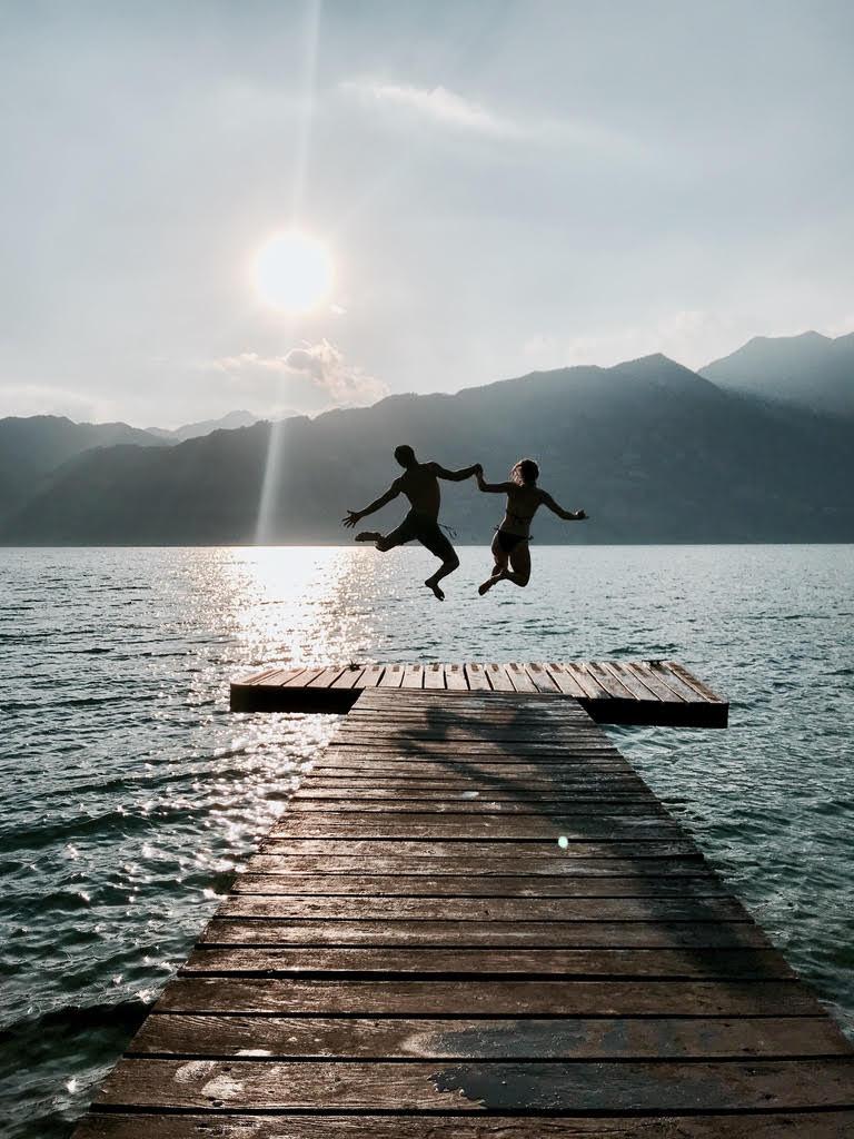 Barča a Marco na gardě skáčou do jezera v plavkách, zachyceni ve skoku.