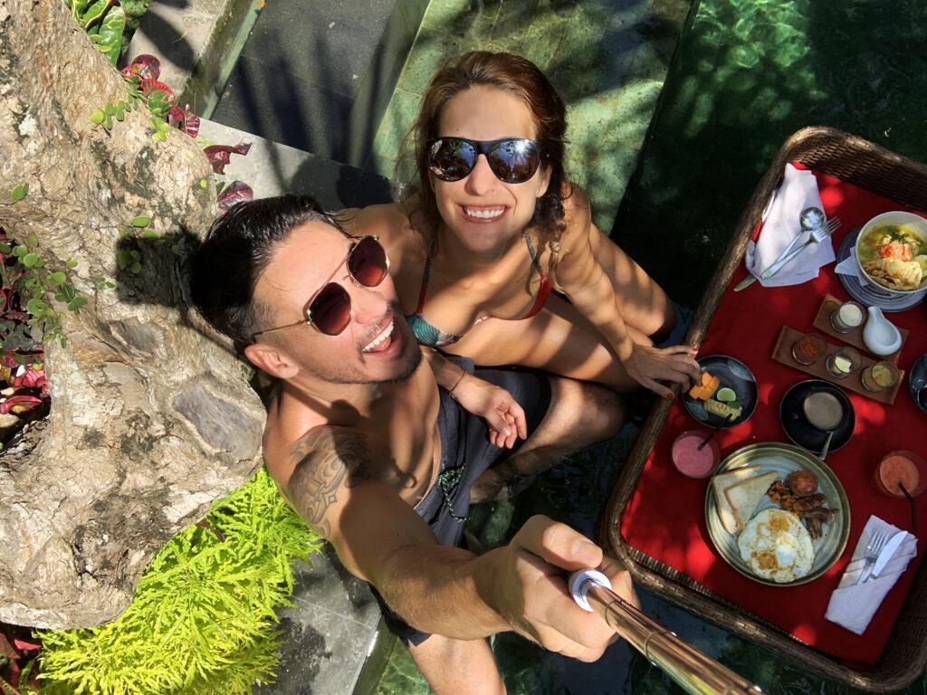 Blogerka Eri Salcmann se fotí s přítelem s pomocí selfie tyče. U toho si pochutnávají na výborném jídle. Sedí u bazénu.