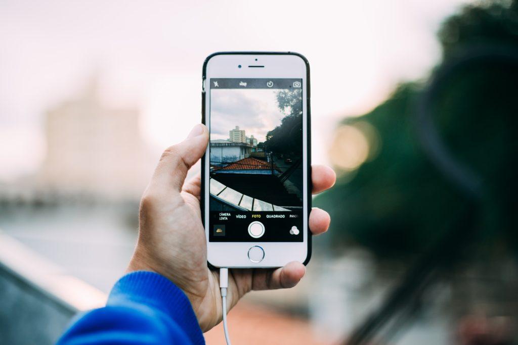 Mobilní telefon v ruce, kterým uživatel právě něco fotí.