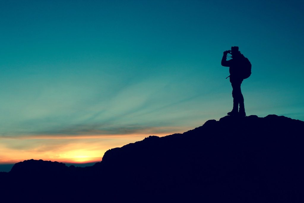 Výletník, který kouká z hory na západ slunce.