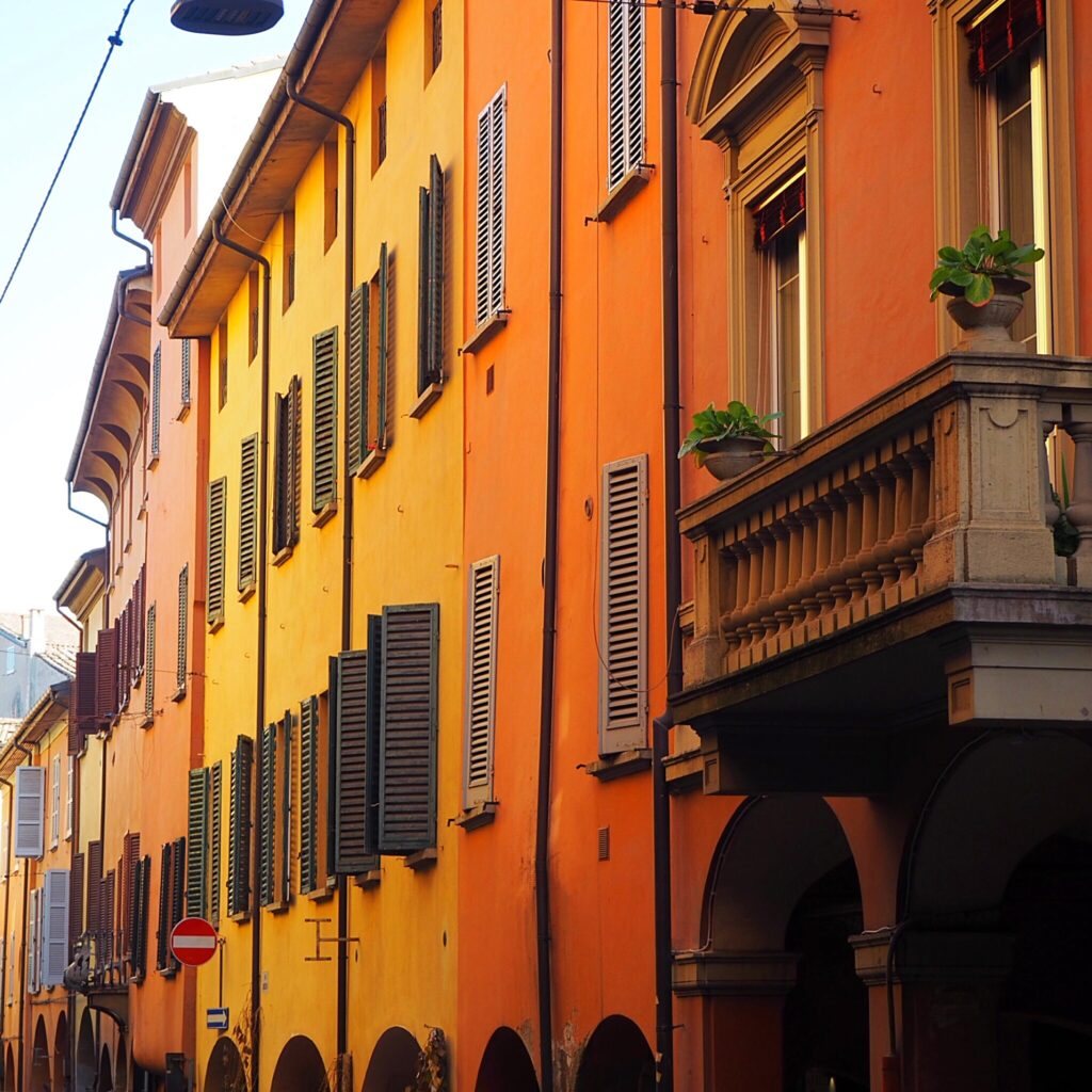 Zákoutí Denisina milovaného města Bologne. Ulice, plná barevných domečků s typickými okenicemi.