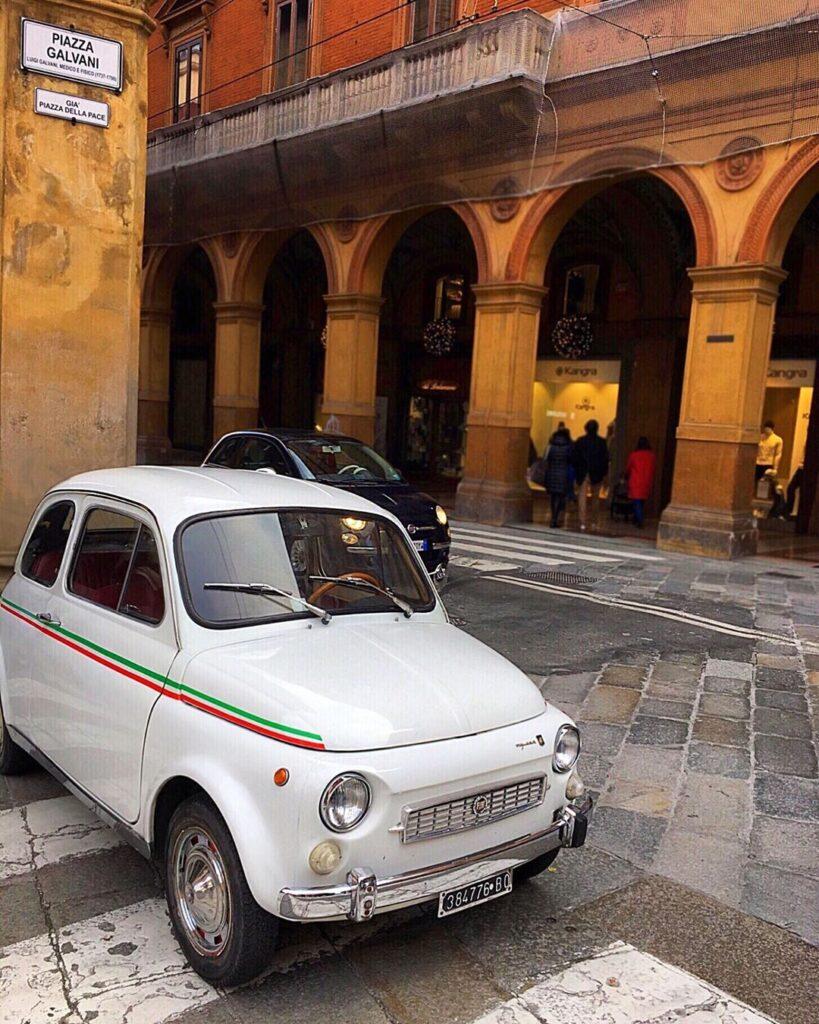 Fiátek 500 v bílé barvě, focený stojící na přechodu na městské ulici.