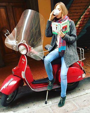 Denisa s učebnicí italštiny v ruce, sedící na italském skútru červené barvy.