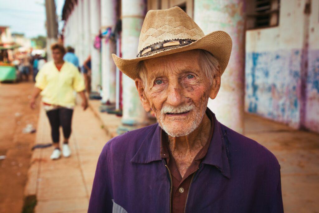 Starý muž v klobouku, stojící na městské ulici.