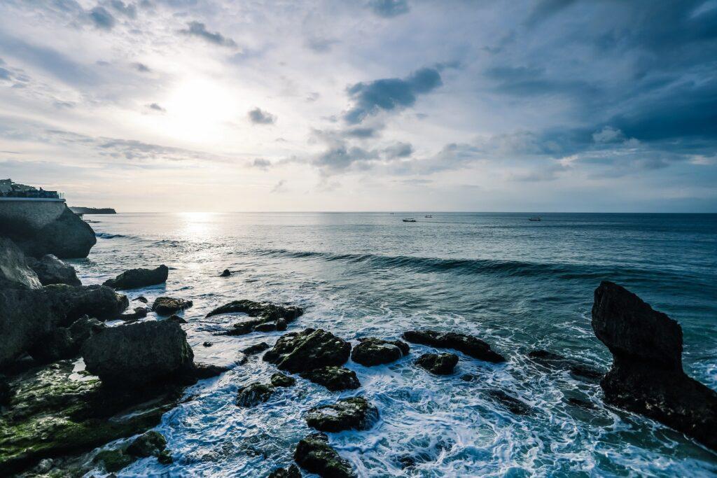Mořské pobřeží při západu slunce se skalami a zpěněným mořem.