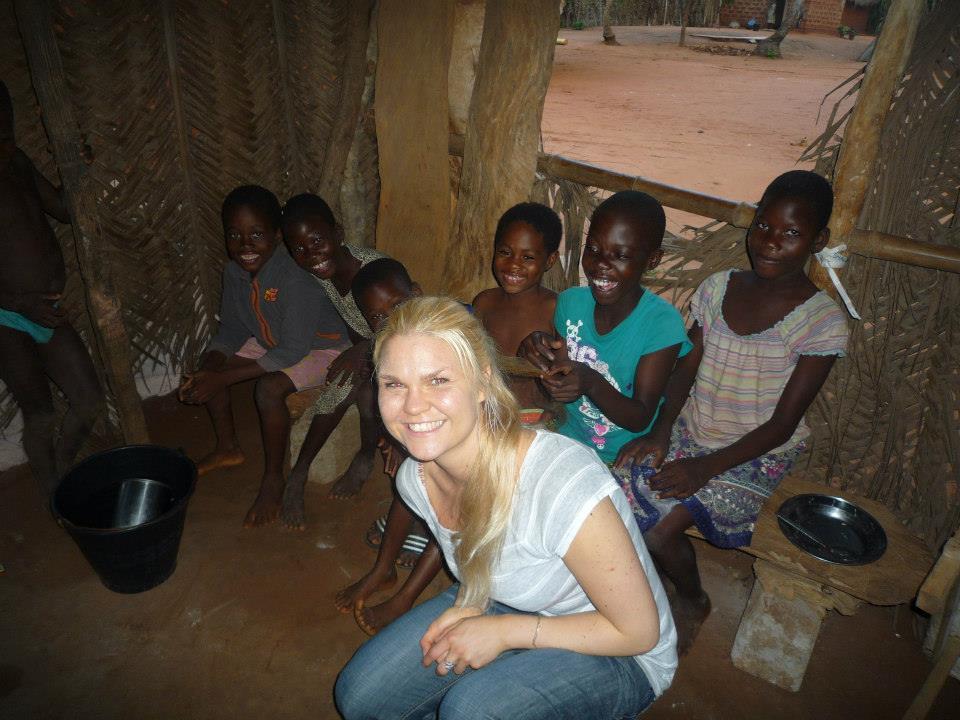Kristýna s dětmi z místní vesnice, v chýši.