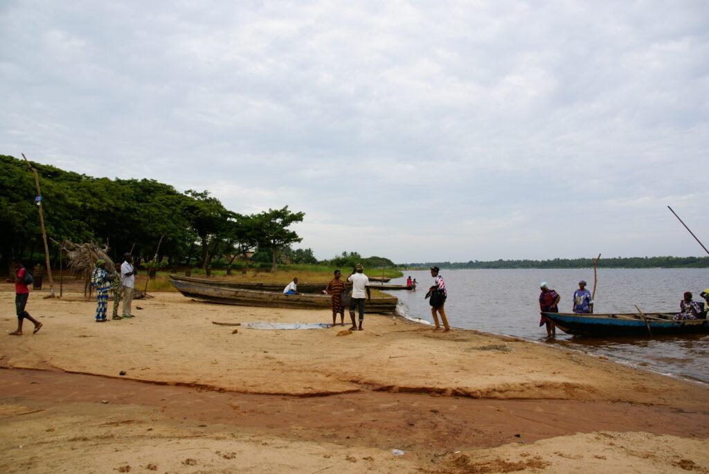 Pláž v místní vesnici s lesem v okolí a několika loďkami.