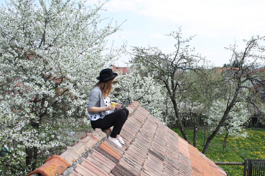 Júlia sedící na střeše s pitím, v klobouku, na pozadí rozkvetlé ovocené stromy.