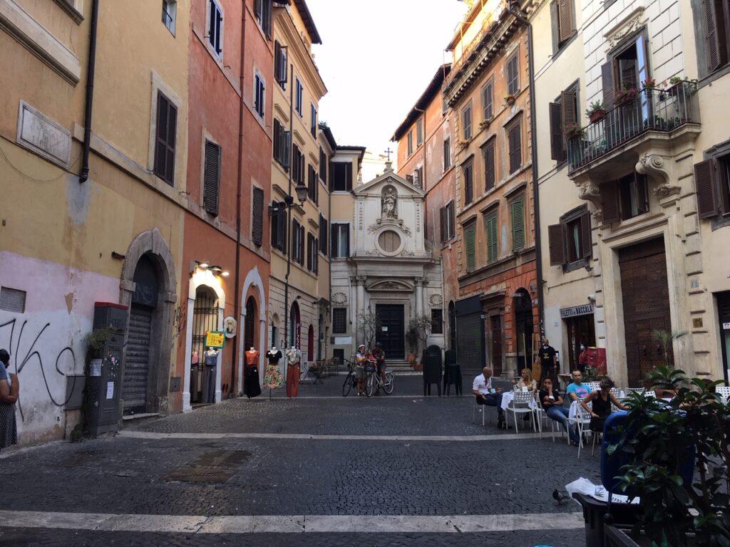 Malý římský kostelíček na konci náměstí, skrytý mezi domy.