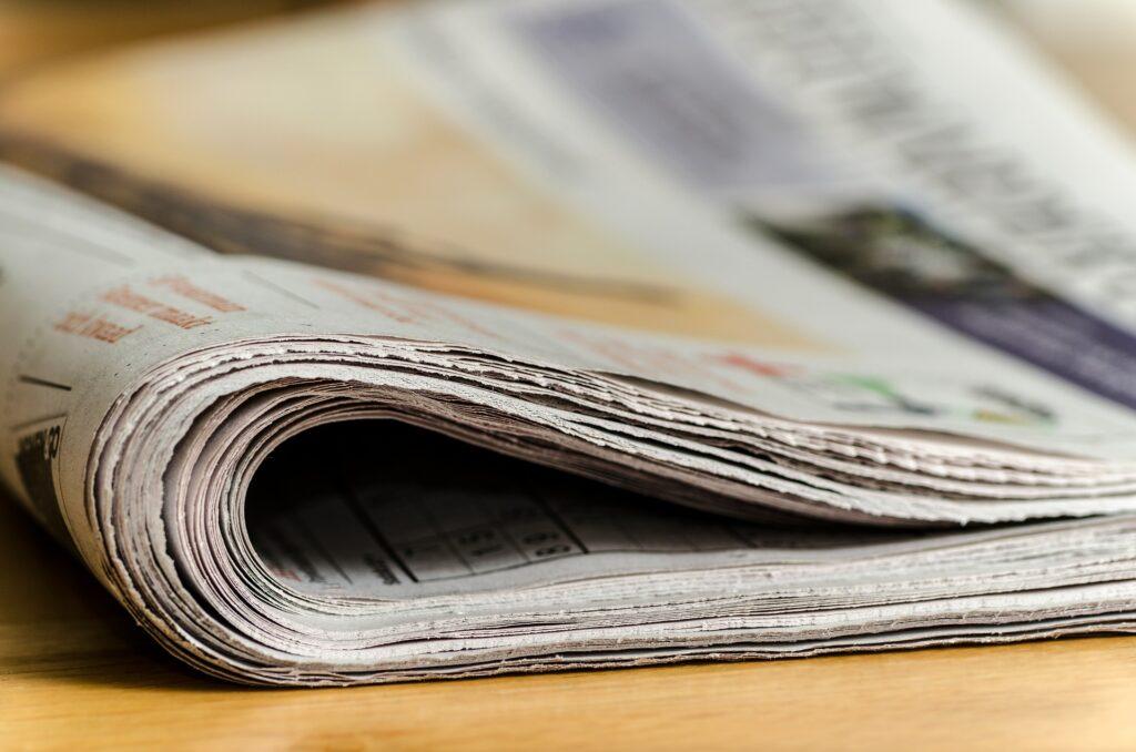 Noviny, přeložené na dřevěném stole.
