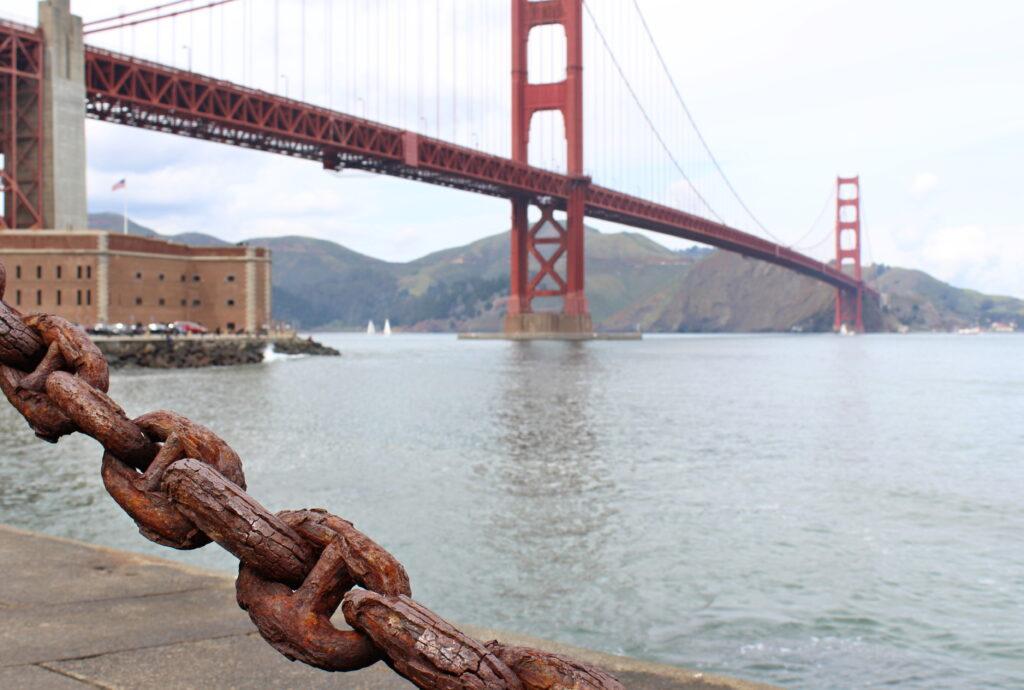Pověstný most Golden Gate s řekou, v pozadí hory.