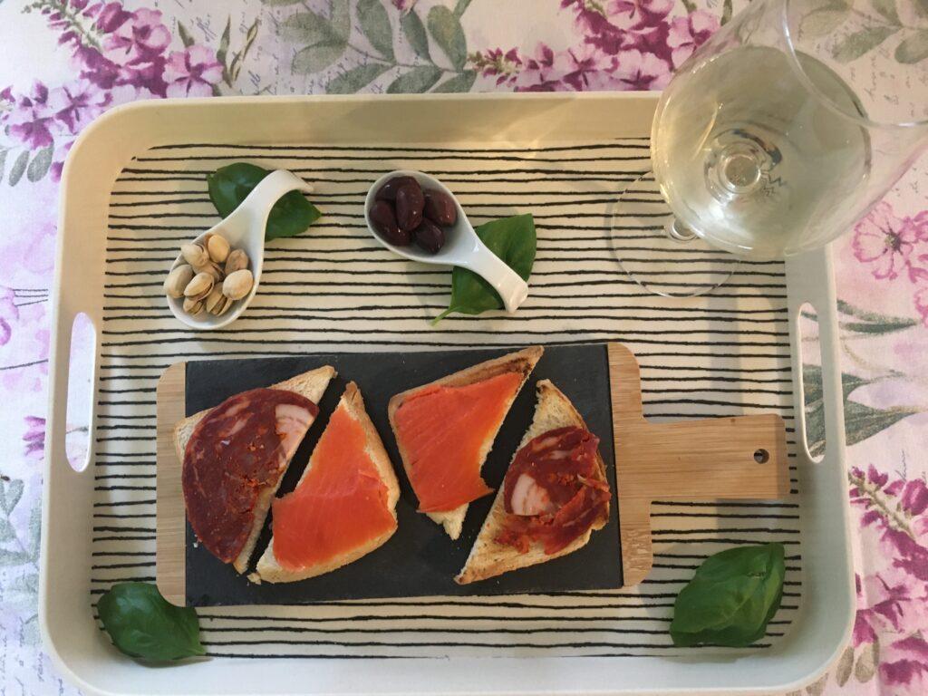 Toasty s lososem a italským salámem, položené na proužkovaném tácku. Vše doplňují olivy, pistácie a lístky bazalky.