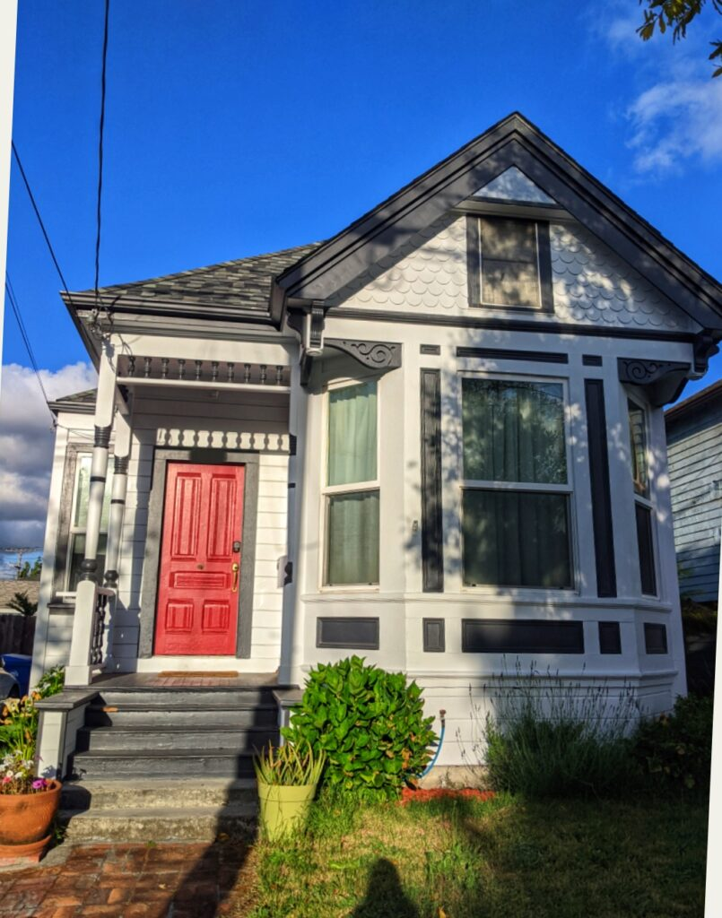 Blančim domeček šedobílé barvy s červenými dveřmi.