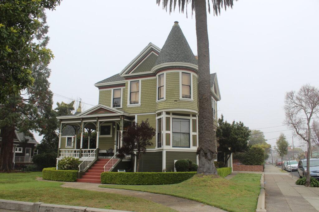 Dům viktoriánského stylu s upraveným živým plotem okolo.