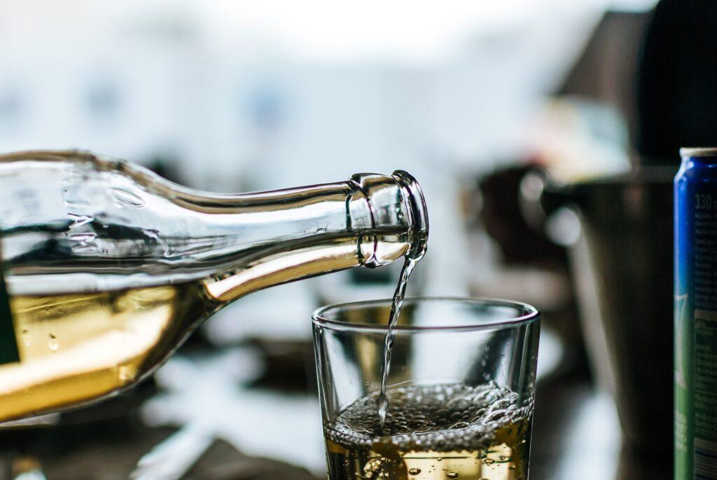 Bílé víno, nalévané do sklenice.